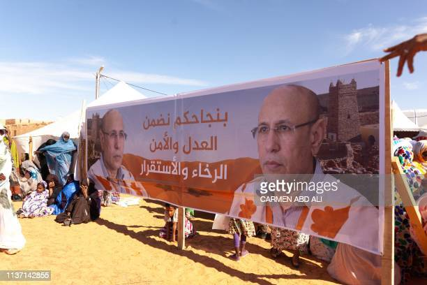 Supporters sit next to a banner whilw they attend a political rally of Union pour la Republique party's candidate Mohamed O Gazhouani supported by...