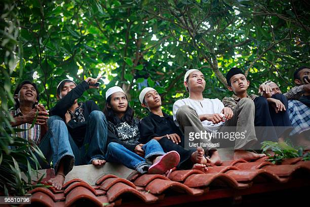 Supporters sit on a roof to look at the funeral of former Indonesia president Abdurrahman Wahid in his East Java hometown on December 31 2009 in...