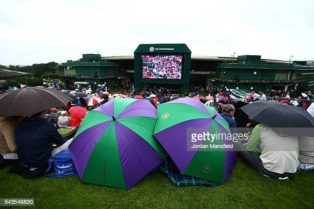 Supporters sit on Murray mound as they take cover from the rain on day three of the Wimbledon Lawn Tennis Championships at the All England Lawn...