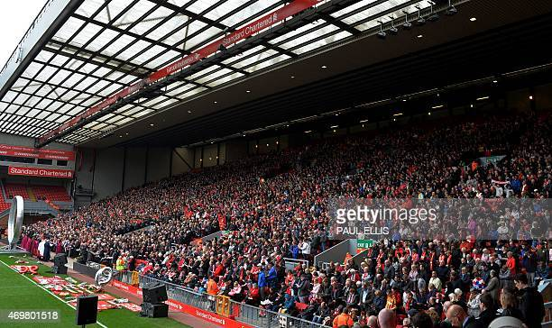Supporters sit on The Kop during a memorial service at Anfield in Liverpool north west England on April 15 on the 26th anniversary of the...