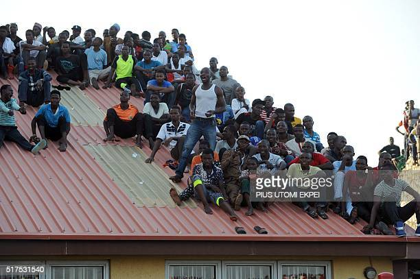 Supporters sit on the roof of a house to watch the African Cup of Nations qualification match between Egypt and Nigeria on March 25 in Kaduna / AFP /...