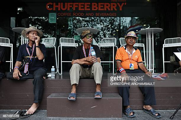Supporters sit outside a coffee shop during an antigovernment march in downtown Bangkok on February 7 2014 Thai antigovernment protesters vowed to...