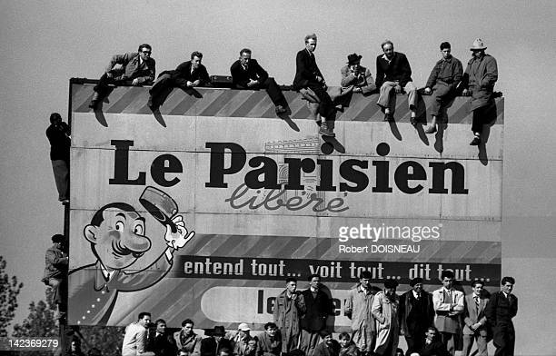 Supporters sitting on a huge advertising hoarding watching the Final of the Coupe de France of football opposing Nice vs Bordeaux in Colombes this is...
