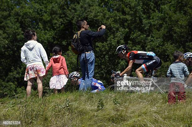 Supporters stand along the road as Luxembourg's Frank Schleck rides past during the 237.5 km sixteenth stage of the 101st edition of the Tour de...