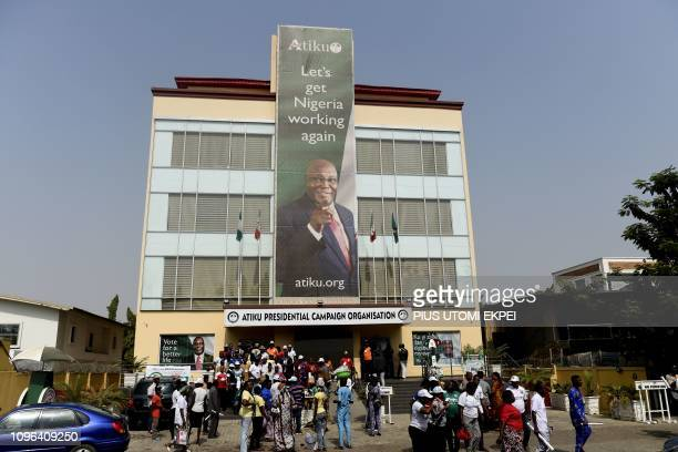 Supporters stand at the campaign headquarters of presidential candidate Atiku Abubakar following the cancellation of a campaign rally by the...