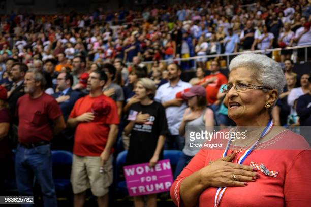 Supporters stand for the National Anthem at the start of a rally featuring US President Donald Trump at the Nashville Municipal Auditorium May 29...