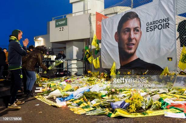 Supporters stand in front of flowers and a giant portrait of Nantes' Argentinian forward Emilianio Sala before the French L1 football match between...