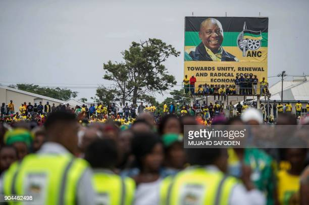Supporters stand under a banner bearing a portrait of African National Congress President Cyril Ramaphosa during the ANC's 106th anniversary...