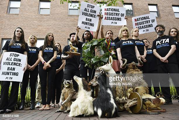 PETA supporters stand with taxidermy animals during a demonstration calling for the end to gun violence outside of the National Rifle Association on...