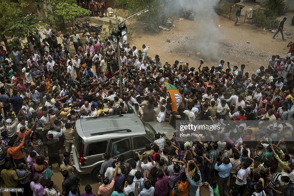 Supporters surround the car of BJP leader Narendra Modi after he visited his mother following his landslide victory in elections on May 16, 2014 in Ahmedabad, India. Early indications from the Indian election results show Mr Modi's Bharatiya Janata Party was ahead in 277 of India's 543 constituencies where over 550 million votes were made, making it the largest election in history.