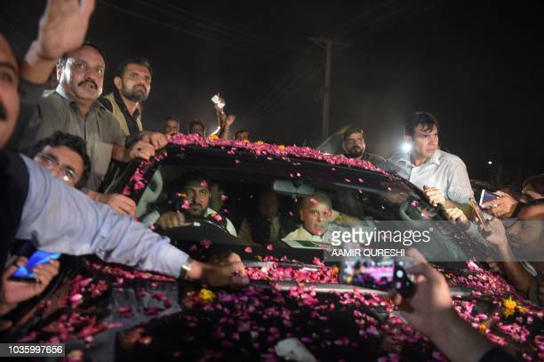 Supporters surround the vehicle carrying former Pakistani primer minister Nawaz Sharif alongside his younger brother Shahbaz Sharif following his...