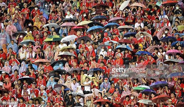 Supporters take cover under umbrellas from a rain storm during a preseason match between Thailand and Liverpool FC at Rajamangala National Stadium on...