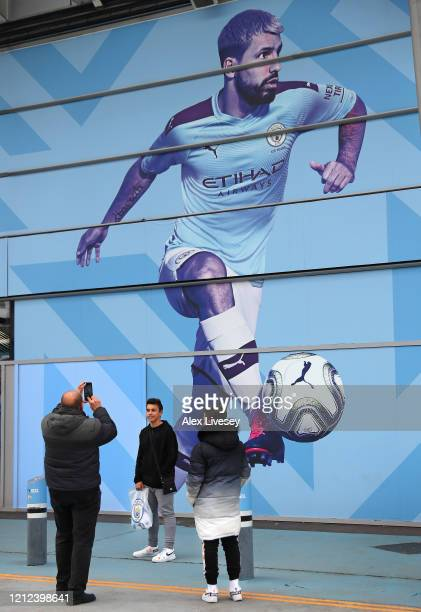 Supporters take photographs outside the Etihad Stadium home of Manchester City FC is seen as the scheduled match to be played today between...