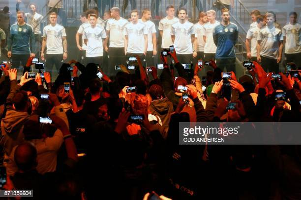 Supporters take pictures with their phones of German national football team's players during the official presentation of the team's new kit for the...