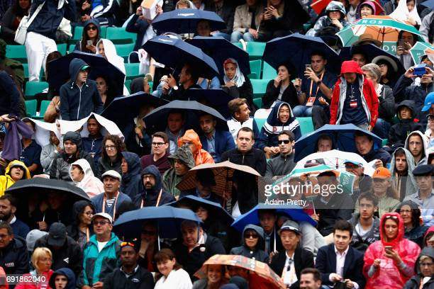 Supporters take shelter from the rain during the mens singles third round match between Gael Monfils of France and Richard Gasquet of France on day...