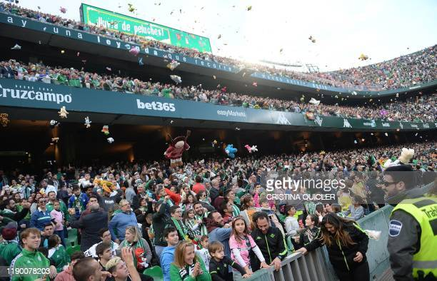 Supporters throw stuffed animals for charity during the half-time break of the Spanish league football match Real Betis against Club Atletico de...