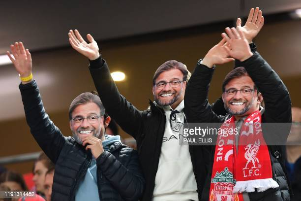 Supporters twear masks of Liverpool's German manager Jurgen Klopp before the English Premier League football match between Liverpool and Sheffield...