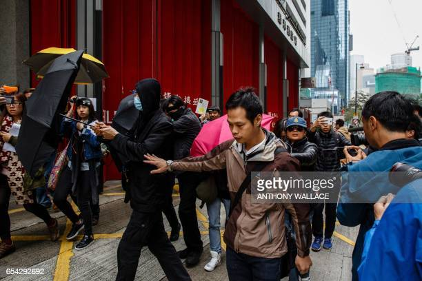 Supporters use umbrellas to cover their faces while surrounded by members of the media as they leave the District Court in Hong Kong on March 17...