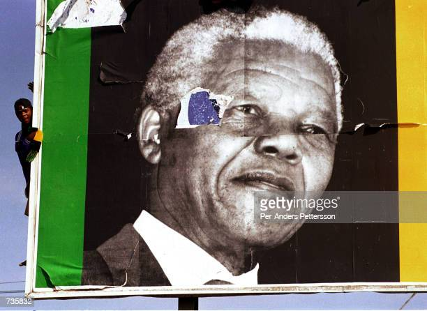 ANC supporters wait for President Nelson Mandela around a billboard April 13 1994 at an ANC rally in Durban weeks before the first democratic...