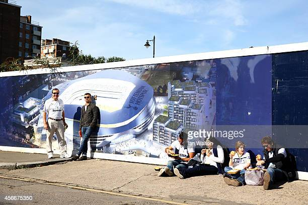 Supporters wait next to a fence displaying a virtual view of the propsed new Tottenham Hotspur stadium development near to the current stadium before...