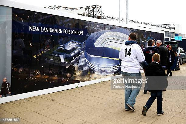 Supporters walk past a fence displaying an image of the proposed new stadium before the Barclays Premier League match between Tottenham Hotspur and...