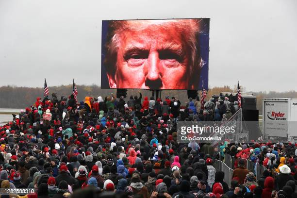 Supporters watch a video of U.S. President Donald Trump while waiting in a cold rain for his arrival at a campaign rally at Capital Region...