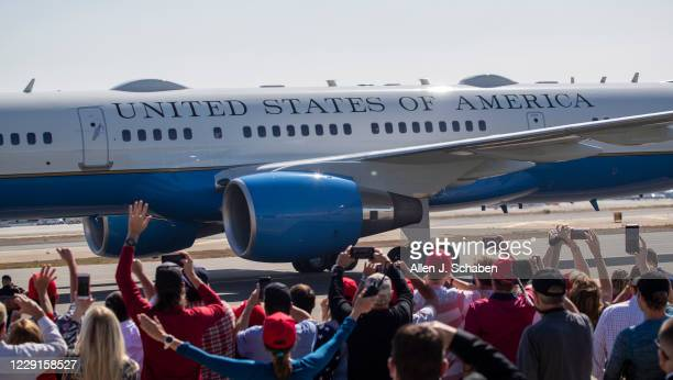 Supporters watch and cheer as President Donald Trump arrives on Air Force One at John Wayne Airport on Sunday, Oct. 18, 2020 in Santa Ana, CA where...