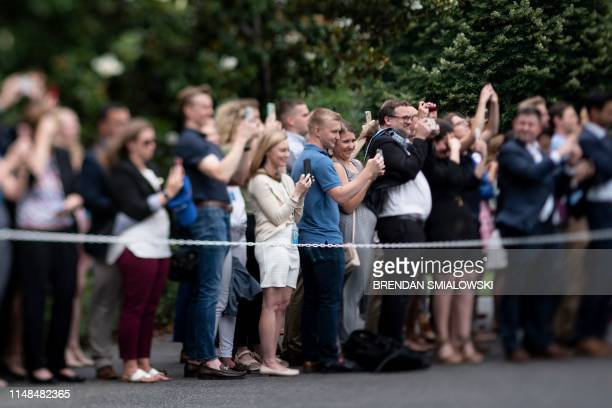 Supporters watch as Marine One lands on the South Lawn of the White House with aboard US President Donald Trump and US first lady Melania Trump on...