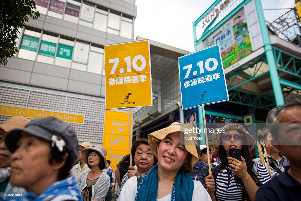 Supporters watch Kazuo Shii, Chairman of the of The Japanese Communist Party (JCP) delivers a campaign speech for his party candidate Taku Yamazoe during the Upper House election campaign outside of Kichijji Station, Tokyo, Japan on July 7, 2016. Japan's upper house election will be held on this coming Sunday July 10, 2016.