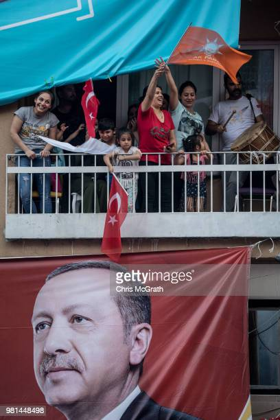 Supporters watch on above an election poster as Turkey's President Recep Tayyip Erdogan speaks during a AK Parti election rally in Kasimpasa on June...