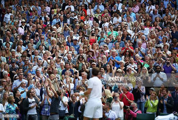 Supporters watch on as Andy Murray of Great Britain celebrates victory during the Men's Singles Semi Final match against Tomas Berdych of The Czech...