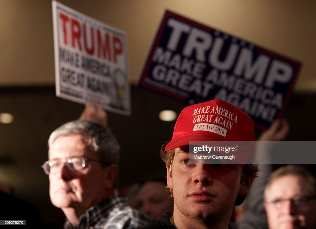 Supporters watch Republican presidential candidate Donald Trump speak after Primary day at his election night watch party at the Executive Court Banquet facility on February 9, 2016 in Manchester, New Hampshire. Trump was projected the Republican winner shortly after the polls closed.