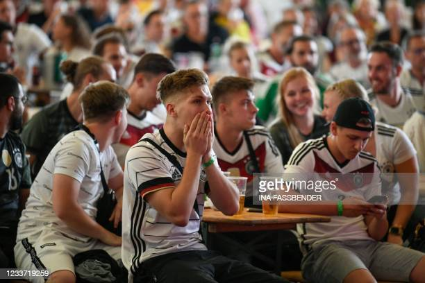 Supporters watch the UEFA EURO 2020 round of 16 football match between England and Germany at the Grugapark in Essen, western Germany, on June 29,...