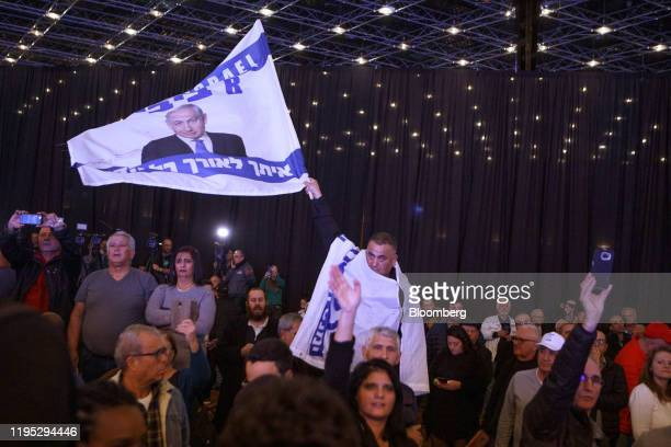 Supporters wave banners during a campaign rally with Benjamin Netanyahu Israel's prime minister for his Likud party in Jerusalem Israel on Tuesday...