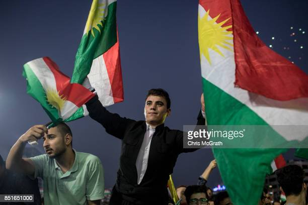 Supporters wave flags and chant slogans inside the Erbil Stadium while waiting to hear Kurdish President Masoud Barzani speak during a rally for the...