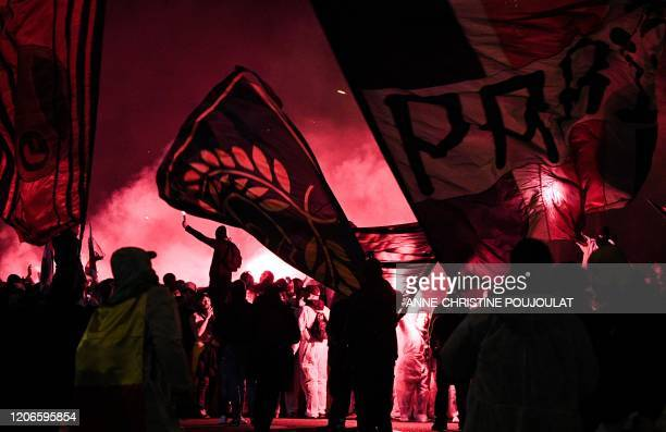Supporters wave flags and chant slogans outside the Parc des Princes stadium ahead of the UEFA Champions League round of 16 second leg football match...