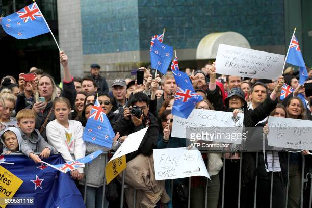 Supporters wave flags and hold up signs as Emirates Team New Zealand parades the America's Cup through the streets of Auckland on July 6 2017 Team...