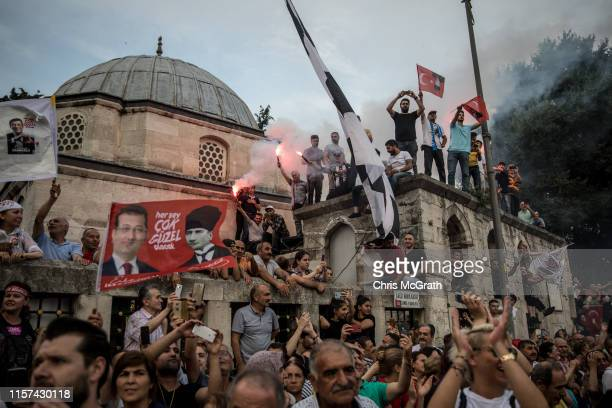 Supporters wave flags and light flares as they listen to Istanbul mayoral candidate Ekrem Imamoglu of the Republican People's Party during a speech...