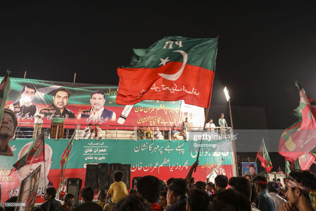 Supporters wave flags during a campaign rally for Imran Khan chairman of Pakistan TehreekeInsaf also known as Movement for Justice not pictured in...