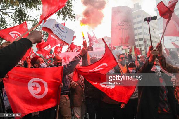 Supporters wave flags of Tunisia and Ennahda as they light smoke bombs during a demonstration held by the Islamist party of Ennahda on Avenue...