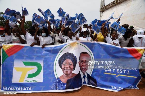 Supporters wave flags to welcome Benin President Patrice Talon and running mate Mariam Talata to a campaign rally at Abomey-Calavi, Benin, on April...