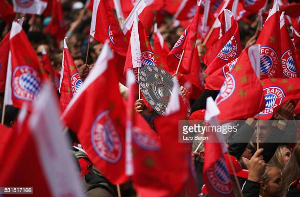 Supporters wave flags waiting players arrival as Bayern Muenchen celebrate winning the Bundesliga at Marienplatz on May 15 2016 in Munich Germany