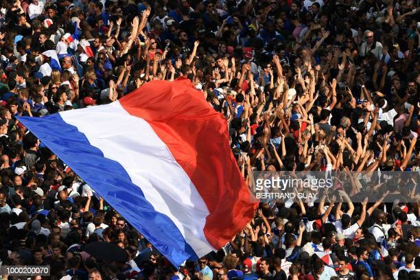 Supporters wave French national flags while they gather at the Place Charles de Gaulle up the ChampsElysees avenue in Paris on July 16 2018 as they...