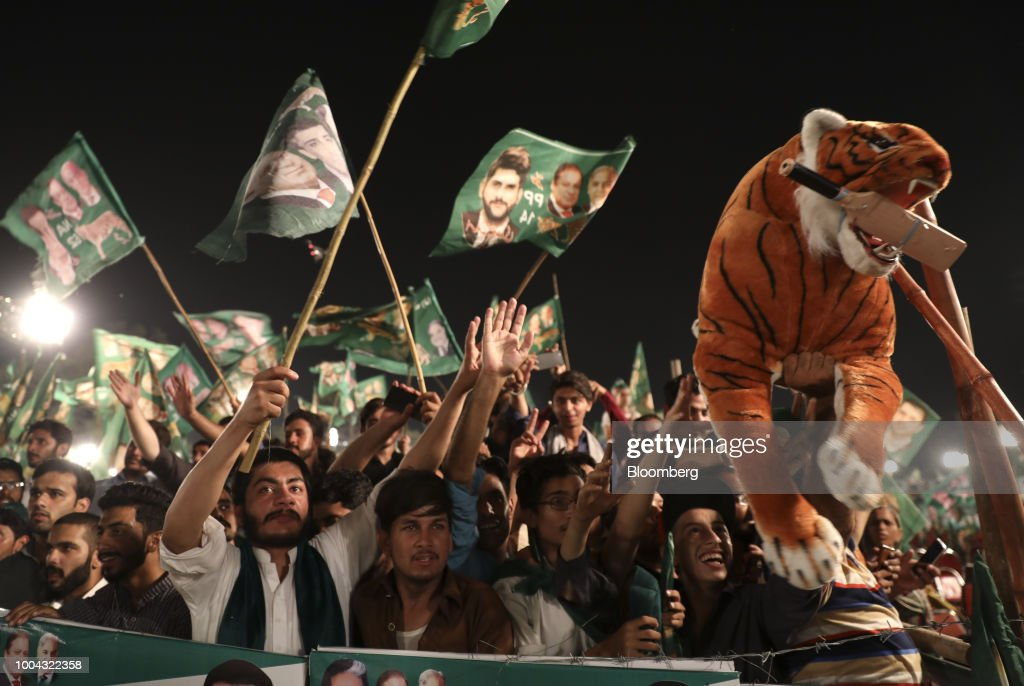 Supporters wave party flags during a campaign rally for Pakistan Muslim LeagueNawaz in Rawalpindi Pakistan on Monday July 23 2018 Whoever wins...
