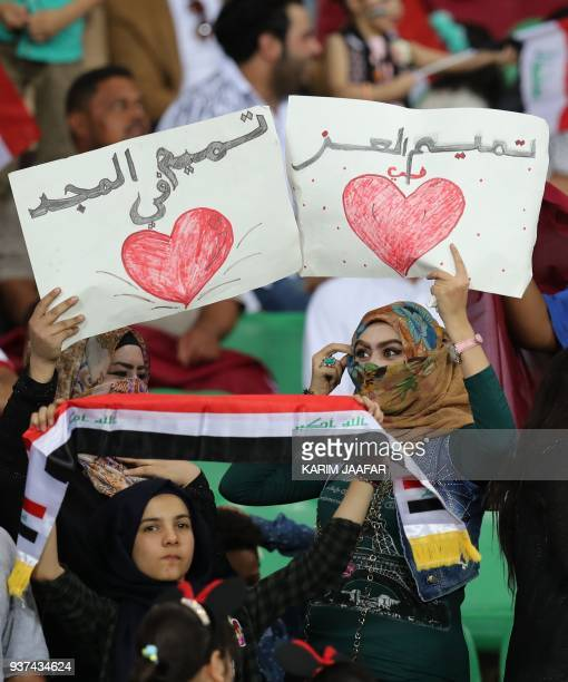 Supporters wave placards reading in Arabic 'Tamim in the heart prior to the international friendly football game Qatar vs Syria at Basra Sports City...