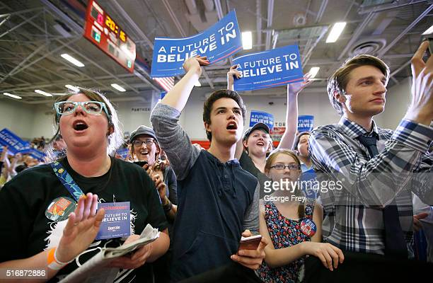 Supporters wave signs as Democratic presidential candidate Bernie Sanders speaks during a campaign rally at West High School on March 21 2016 in Salt...