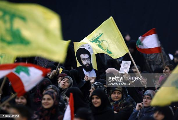 TOPSHOT Supporters wave the flag of Lebanon and the Shiite movement Hezbollah alongside a poster of former Hezbollah leader Abbas alMussawi as they...