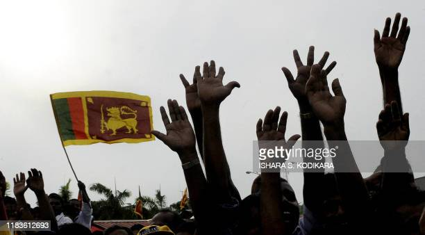 Supporters wave the Sri Lankan flag as they celebrate the return of Sri Lankan President Mahinda Rajapakse from Jordan to a hero's welcome in Colombo...