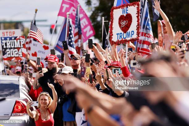 Supporters wave to outgoing US President Donald Trump as he returns to Florida along the route leading to his Mar-a-Lago estate on January 20, 2021...