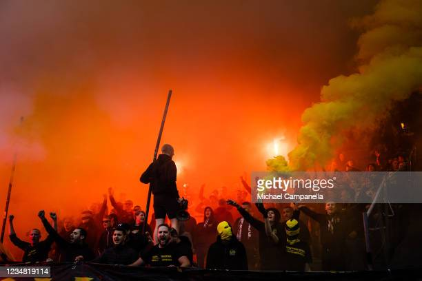 Supporters waves flags and light flares during the Allsvenskan match between AIK and BK Hacken at Friends Arena on August 22, 2021 in Stockholm,...